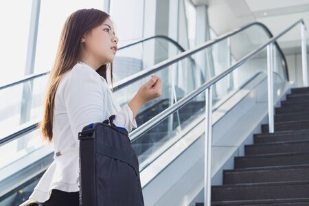 Young Asian business woman going to work by walking on the stairs and holding her bag. Business and finance concept.