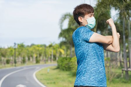 Young male wearing medical mask and stretching his arms before workout training session at the park. Stay in fit during quarantine in the days of the Corona Virus or Covid-19