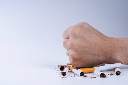 Stop smoking. Close up of male hand breaking cigarette with his fist. Tobacco Day. Cigarette on white background.