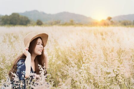 Summer portrait of young hipster woman sitting in meadow on sunny day.young slim beautiful woman, bohemian outfit, indie style, summer vacation, sunny, having fun, positive mood, romantic, woman in hat Imagens