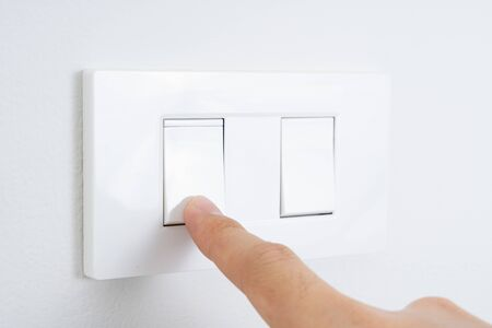 Close up finger turn on or off on white light switch with white wall at home. Power and energy saving. Copy space for text.