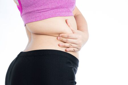 Fat woman holding excessive fat belly lower back, overweight fatty belly isolated on over white background. Diet lifestyle, weight loss, stomach muscle, healthy concept. Standard-Bild
