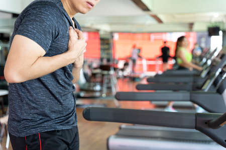 A man feeling exhausted and suffering from heart pain and injury while running on treadmill at fitness gym. Sport, health care and medical concept. Stock Photo