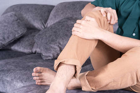 Young man suffering from knee pain while sitting on sofa at home. Healthcare medical or daily life concept.