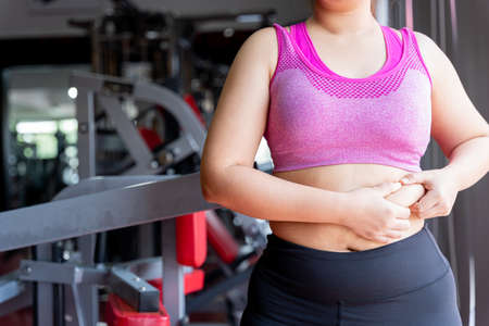 Fat woman holding excessive fat belly, overweight fatty belly at fitness gym. Diet lifestyle, weight loss, stomach muscle, healthy concept.