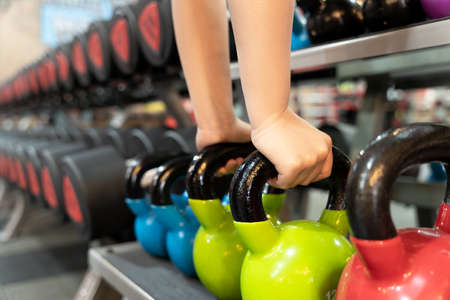 Closeup female hands pick up kettlebell from the set of dumbbell for exercise and strength training. sport, fitness, health, lifestyle and people concept Reklamní fotografie