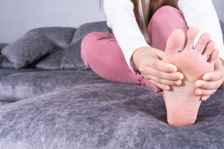 Young woman suffering from foot pain while sitting on sofa at home. Healthcare medical or daily life concept.