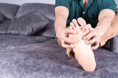 Young man suffering from foot pain while sitting on sofa at home. Healthcare medical or daily life concept.