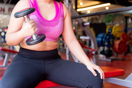 Fat woman holding dumbbell and excessive fat belly, overweight fatty belly at fitness gym. Diet lifestyle, weight loss, stomach muscle, healthy concept.