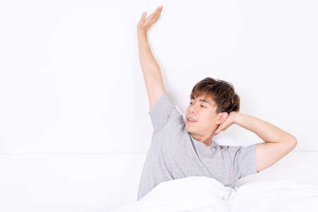 Young Asian man stretching in bed after wake up from the good comfortable bed. Healthcare medical or daily life concept. Foto de archivo