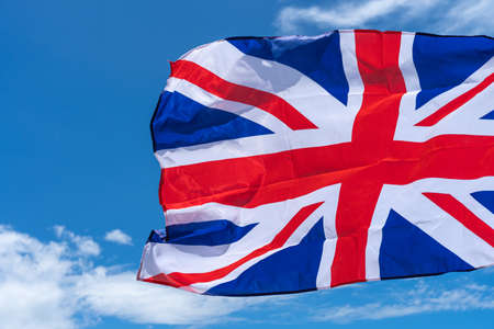 Waving UK flag under blue sky background.
