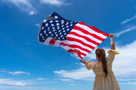 woman standing and holding USA flag under blue sky. Stock Photo