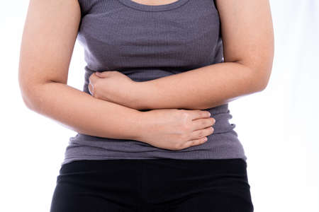 Woman suffering from stomach pain and injury isolated white background. Health care and medical concept. Stock Photo