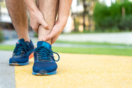 Male runner athlete leg injury and pain. Hands grab painful leg while running in the park.