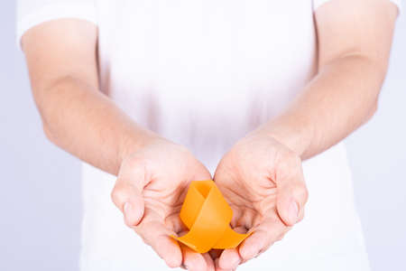 World kidney day, hands holding orange ribbon awareness of kidney disease isolated white background.