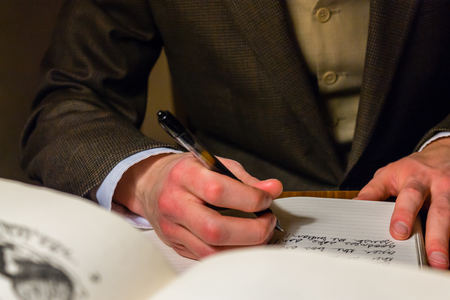 Man writing a letter while reading books
