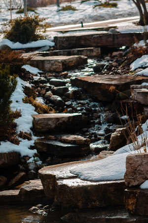 Waterfall trickling down some stones on a winter day 版權商用圖片