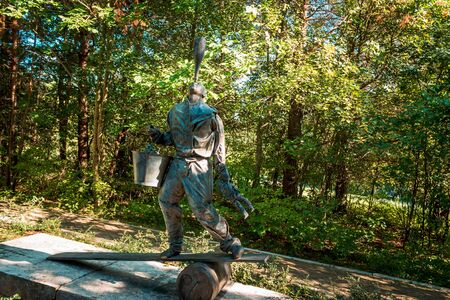 Landscape shot of a statue of a man balancing a bottle on his nose while on a board at the Frederik Meijer Gardens