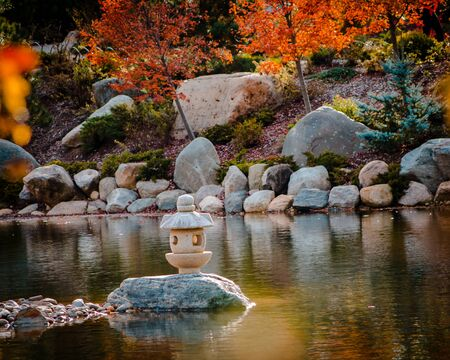 Beautiful shot of the autumn landscape and an isolated stone lantern statue