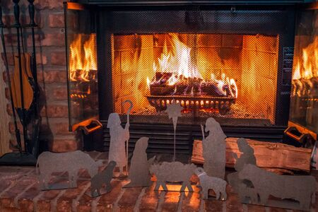Metal nativity scene in front of a lit fireplace during Christmas time