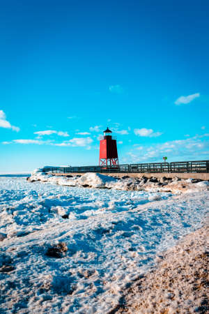A view of the South Pier Light house and the ice dunes off of Lake Michigan in Charlevoix MI 版權商用圖片