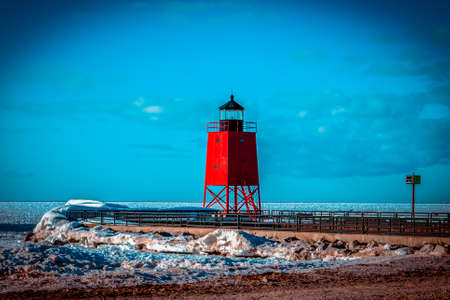 The bright red lighthouse standing out over a frozen beach in Charlevoix Michigan