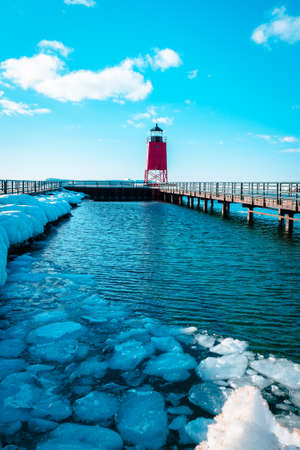 Small icebergs melting at the South Pier Lighthouse off of Lake Michigan in Charlevoix Michigan in winter