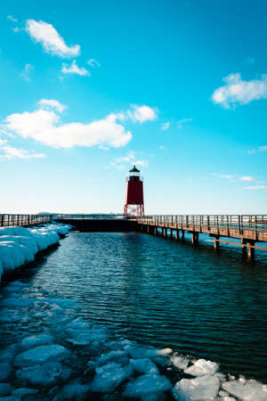 Lake Michigan thawing out at the South Pier lighthouse in Charlevoix MI during the winter 版權商用圖片