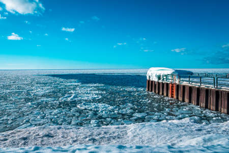 Charlevoix Michigans pier looking out over a frozen lake Michigan