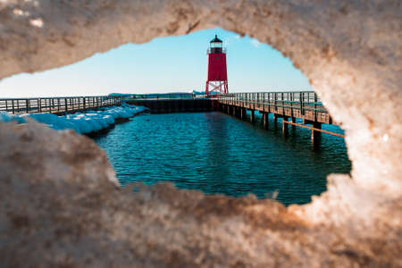 Looking through melting ice at Charlevoix Michigans lighthouse