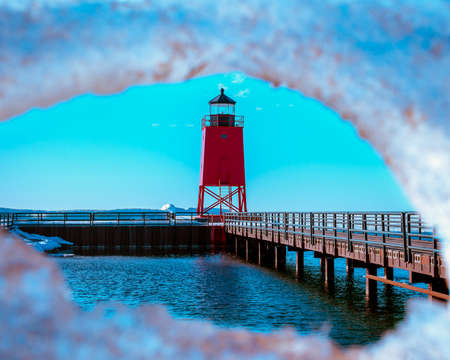 Shot of a red light house through an ice sheet in Charlevoix Michigan