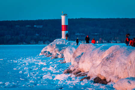 Tourists visiting a frozen lighthouse in Petoskey Michigan