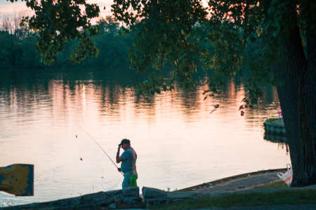 Grand Rapids, MI /USA - August 31st 2018: Fisherman on the Grand River at sunset in Grand Rapids Michigan