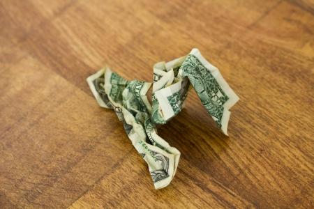 scrunched: A scrunched up one dollar bill on a wooden surface Stock Photo