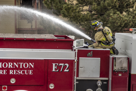 engine powered: Fireman behind hose fighting an apartment fire. Editorial