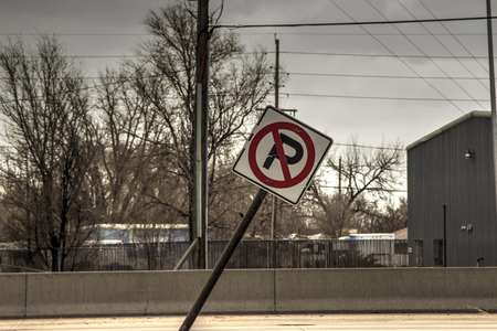 no parking sign: Leaning No Parking sign with urban neighorhood background. Stock Photo