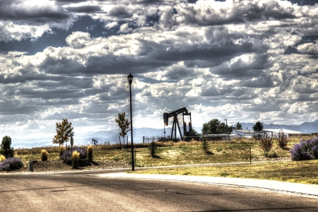 upcoming: A working oil well in an upcoming suburban neighborhood. Stock Photo