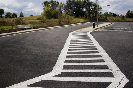 keep an eye on: A pedestrian crosswalk through parking lot blacktop. Stock Photo
