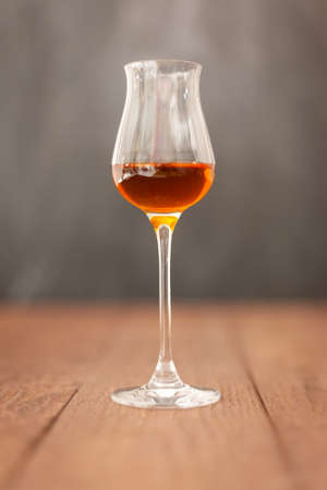 Grappa glass with brandy or sherry or calvados on wooden table with light grey background.