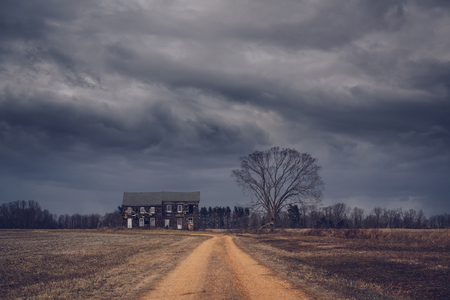 Dirt road leading to a haunted house with dark rain clouds