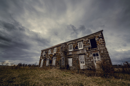 Creepy abandoned home with dark rain clouds above