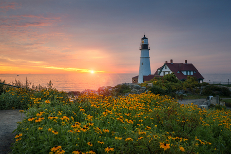 Beautiful sunrise at Portland Head Light with flowers in the foreground Editorial