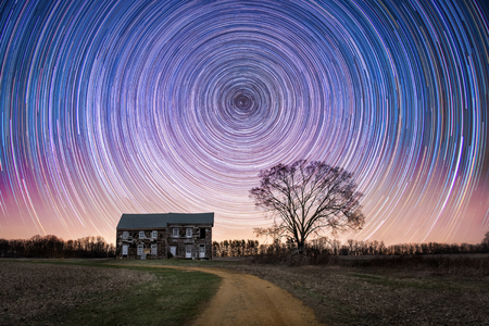 Star trails over an abandoned farm house Stock Photo