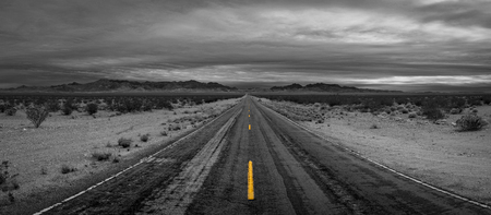 Black and white with selective color dashed road lines for a road to nowhere
