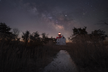 Path leading towards the East Point Lighthouse under the Milky Way Galaxy Фото со стока