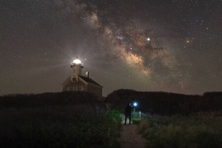 A person standing on a path leading towards North lighthouse at night Фото со стока
