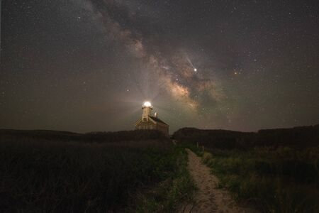 Path leading towards North Lighthouse and the Milky Way Galaxy Фото со стока