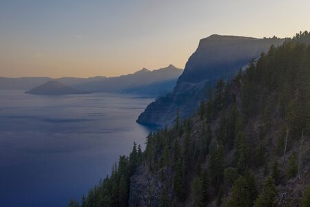 Aerial view of cliffs surrounding Crater Lake at sunset in Oregon