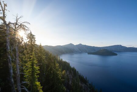 Sun rays shining through trees over Crater Lake, Oregon.