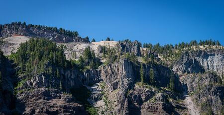 Rocky cliffs surrounding Crater Lake in Oregon